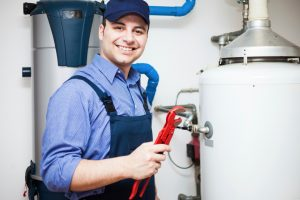 a plumber smiles as he works on a plumbing service in allendale
