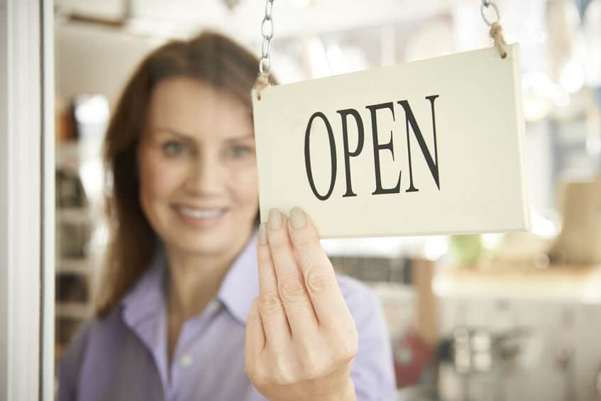 """woman turning business sign to """"open"""" after commercial services in bergen county nj"""