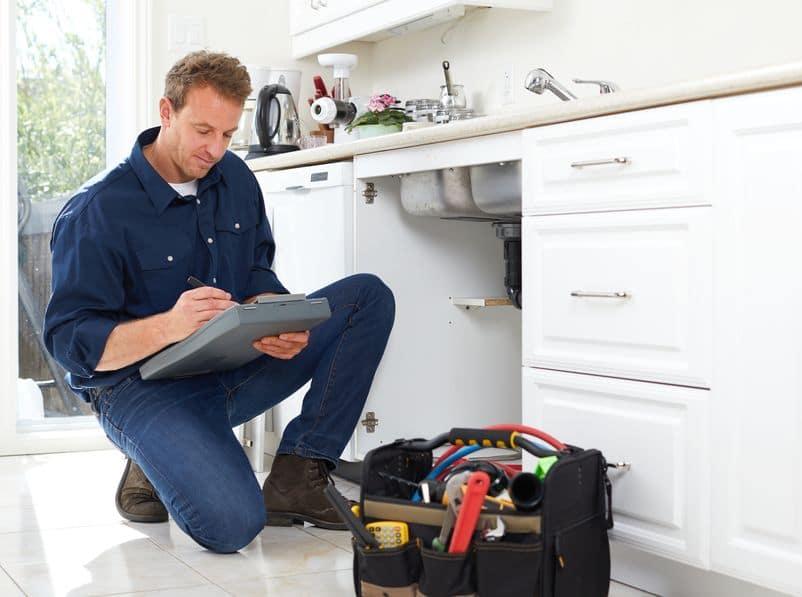 image of a teaneck nj plumber performing kitchen plumbing repairs
